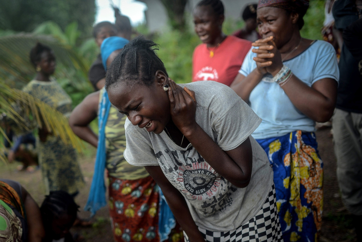 KENEMA, SIERRA LEONE - AUGUST 25: Relatives of Baindu Koruma (28) died due to the Ebola virus, mourn in Lango village, Kenema, Sierra Leone on August 25, 2014. Ebola, a contagious disease for which there is no known treatment or cure, has claimed hundreds of lives in Sierra Leone, Guinea and Liberia.  (Photo by Mohammed Elshamy/Anadolu Agency/Getty Images)